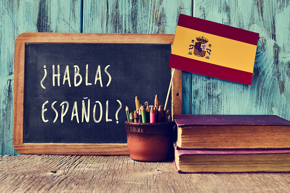 A chalkboard with the question 'Do you speak Spanish?'